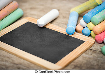 Slate with copyspace and colorful crayon on wooden table -...
