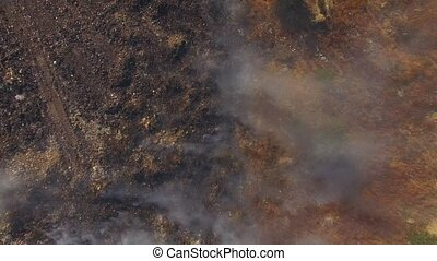 Burning Dump Site Producing Smoke - AERIAL VIEW. Zoom out...