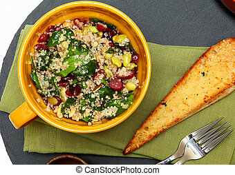 Quinoa Spinach Cranberry Salad and Garlic Toast on Table.