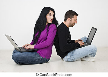 Woman spying into her husband laptop - Couple sitting back...