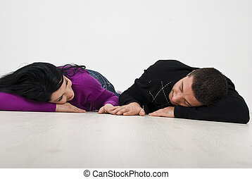 Young couple lying and holding hands - Young couple lying...