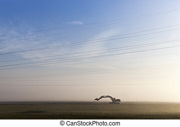 Excavator in a fog - Excavator standing in the field of...