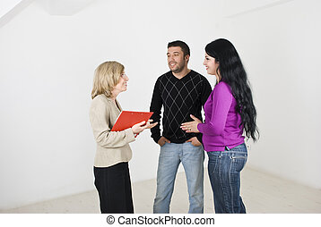 Estate agent woman conversation with young couple - A real...