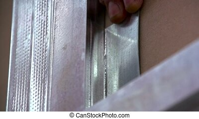 Screw twists into drywall profile. - Construction worker...