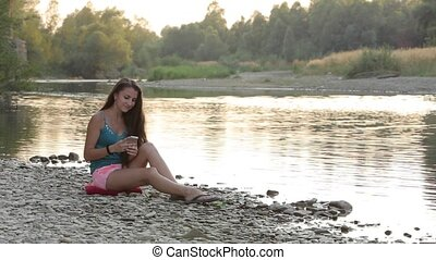 Girl Sitting on the River Bank of Phone Viewing Mail - girl...