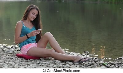 Girl Sitting on the River Bank With the Phone Chooses...