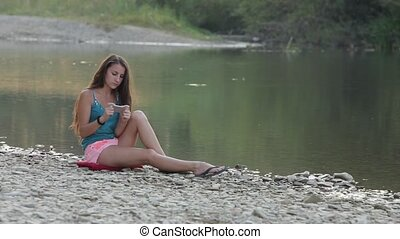Girl Sitting on the River Bank With the Phone Plays the Game...