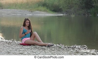 Girl Sitting on the River Bank With the Phone, the Phone...