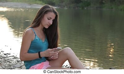 Girl Sitting on the River Bank With Phone Typing - girl of...