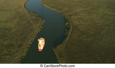 View of air balloon flying over river and fields - Top view...
