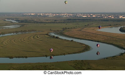Hot air balloons flying over river in countryside - View of...