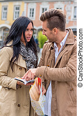 couple on a city break - young couple with a map and guide...