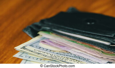 Money in a Wallet Rotating on a Wooden Table - Money dollars...