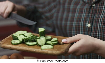 Close up of young housewife putting fresh greencucumbers into plate with a healthy salad.