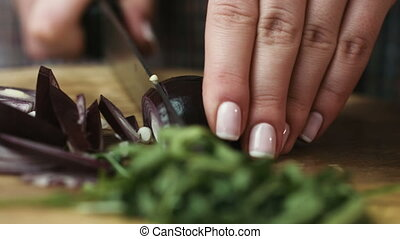 Young housewife slicingred onion into rings at the tablewith a knife on a cutting board.