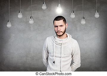 Young man thinking on the gray background with light bulbs