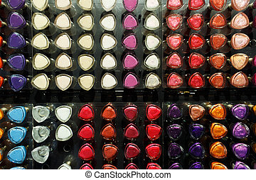 Set of different nail varnishes on shelves in cosmetic store...