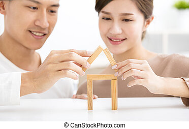 happy young couple playing with toy blocks