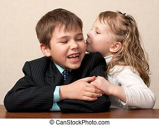 Wispering secrets in the classroom - A girl is wispering to...