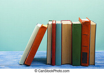 Stack of hardback books on wooden table. Back to school....