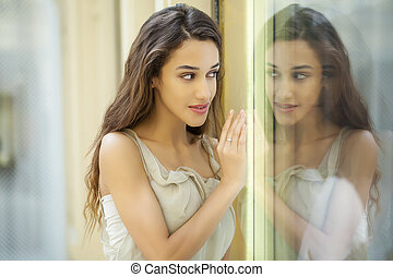Portrait of a beautiful brunette. Reflection in the mirror