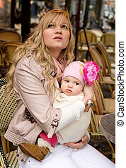 Beautiful young mother with her baby daughter in a Parisian...
