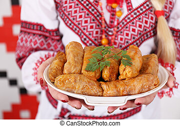 Cabbage rolls on a plate in a female hand