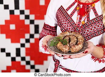 Home sausage on a plate in the hands of women