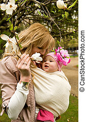 Beautiful young mother with her baby daughter in a garden at spring