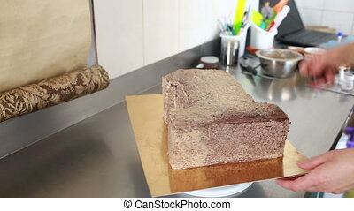 pastry chef decorates a cake in a candy store sponge cake