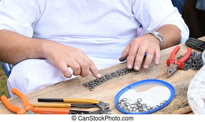 Man making coat of mail - Man using tools and metal rings to...