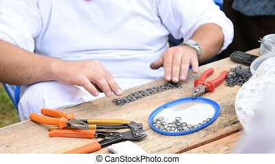 Man making chain armor using tools and metal rings. He...
