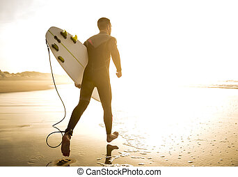 Lets catch some waves - A surfer with his surfboard running...