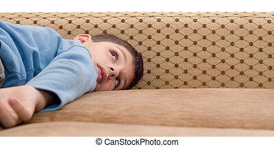 boy in blue lying on sofa