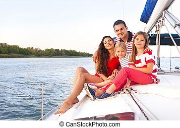 Beautiful happy family with two daughters having great time at the yacht
