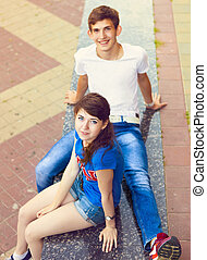 Cute young beautiful teens sitting in city near university...