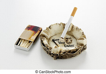 Cigarette in skull ashtray with matches - Cigarette in skull...