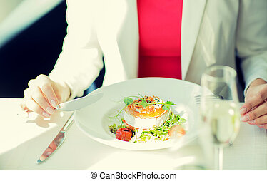 close up of woman eating salad at restaurant - people,...