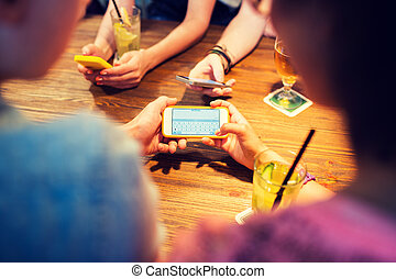 close up of hands with smartphones at restaurant