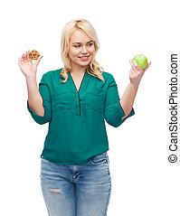 smiling woman choosing between apple and cookie - healthy...