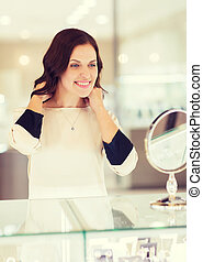 happy woman choosing pendant at jewelry store - sale,...