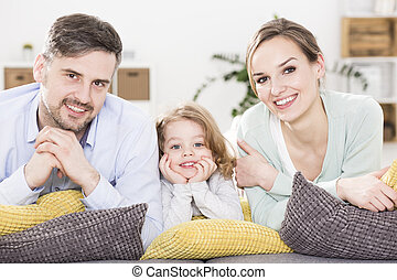 Leisure time with family - Smiling man, woman and small girl...