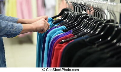 beautiful woman shopping in clothing store chooses dress