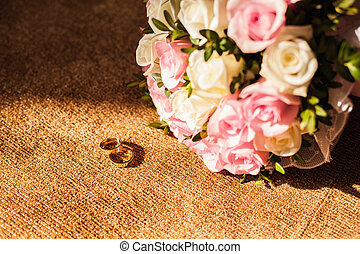 The wedding rings with pink roses on the carpet texture