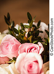 The wedding rings with pink roses close up