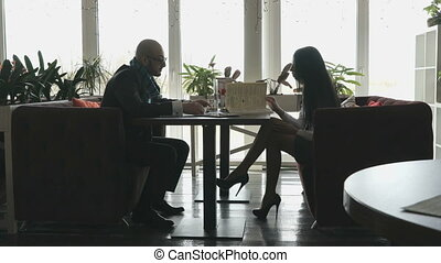 Young beautiful couple sitting in restaurant