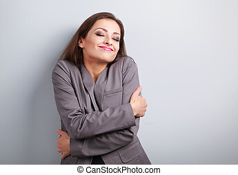 Happy business woman hugging herself with closed eyes and...