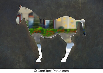 Cut out horse in a dark metal wall