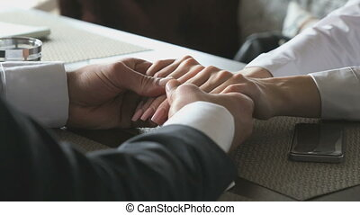 Young couple holding hands sitting at table