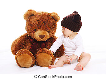 Baby playing with big teddy bear toy on white background